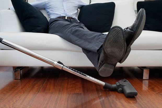 Foto Staubsaugen unter Füßen von Mann Couch